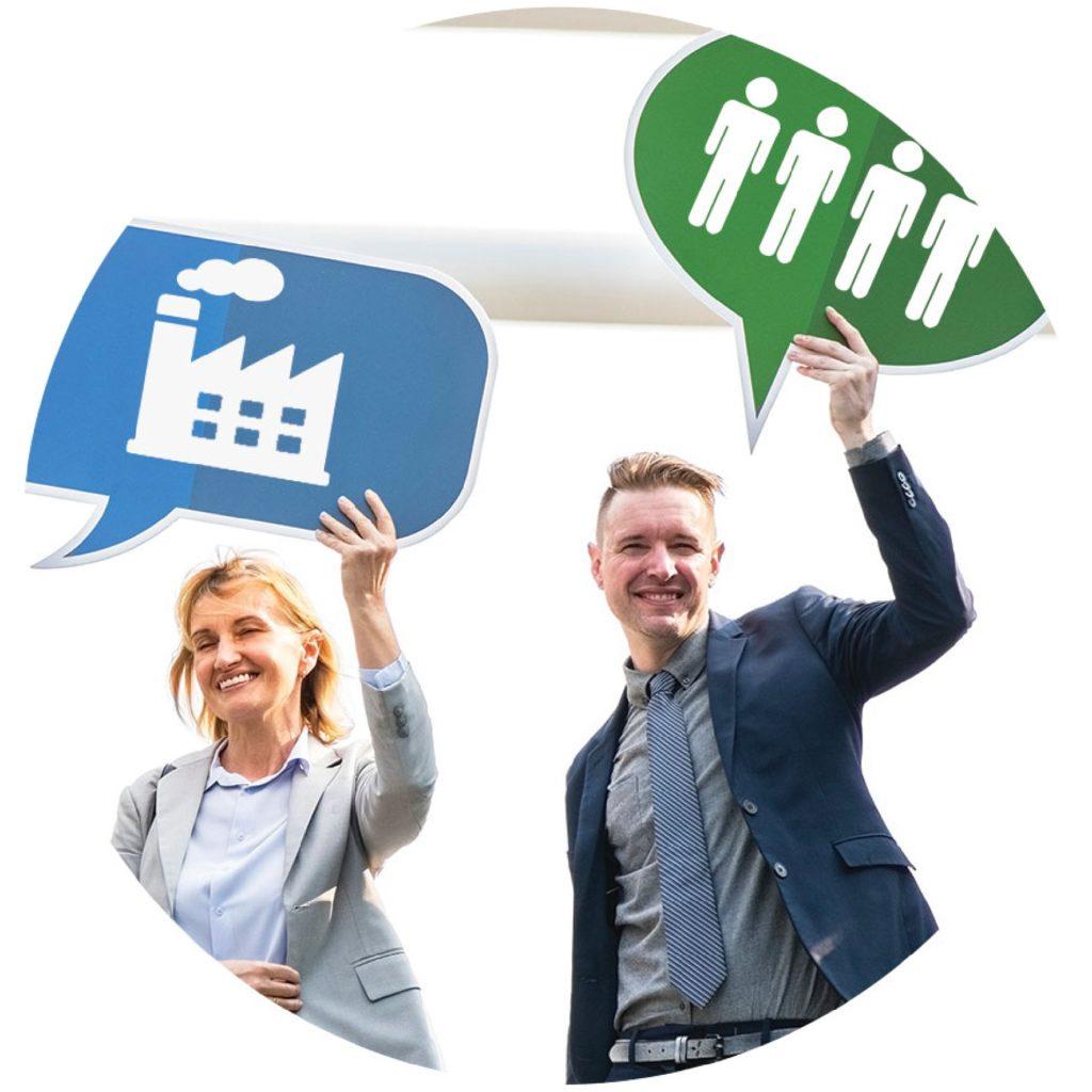 A képen egy hölgy látható, aki a kezében tart egy táblát, melyen egy gyárépület látható. Mellette egy férfi áll, az ő tábláján 4 ember látható.