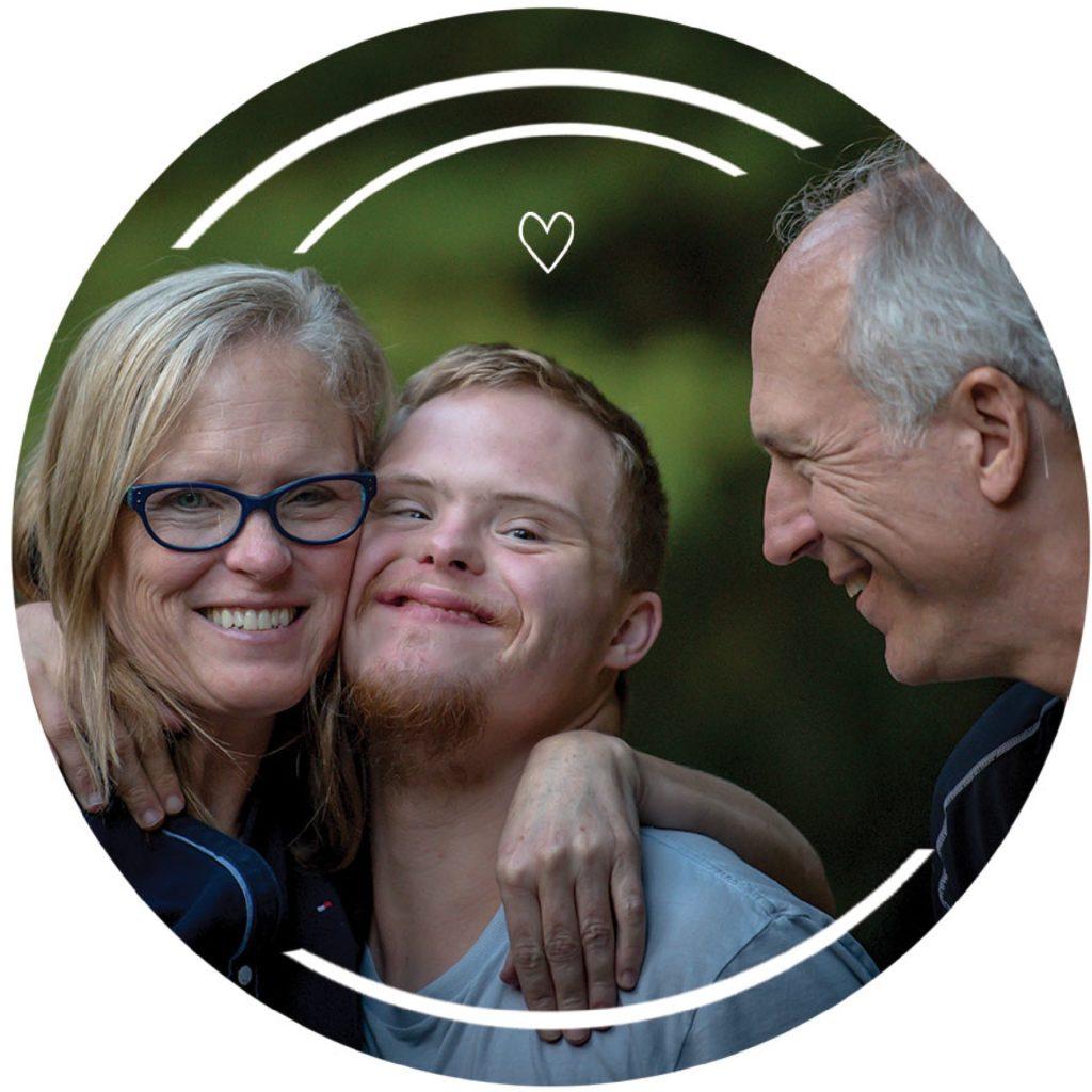 A képen egy édesanya látható down szindrómás fiával ölelik át egymást. Mellettük állva mosolyogva nézi őket az édesapa.