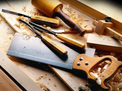 A képen asztalos szerszámok láthatóak falapokkal és faforgáccsal körbevéve.