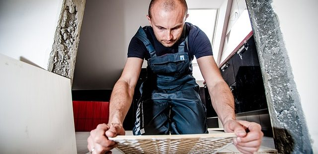 A képen egy férfi burkoló látható munka közben. Egy járólapot helyez a földre.