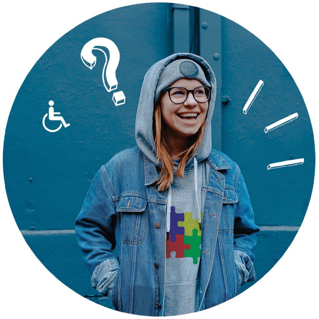 A képen egy fiatal lány látható. Hosszú, világos színű haja van és szemüveget visel. A fején egy sapkát visel, amire a pulóvere kapucniját is felhúzta. Pulóverén kirakó darabok láthatók. Mosolyog.