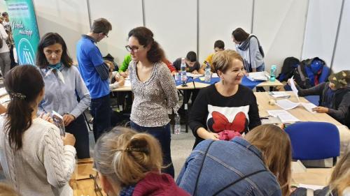 A képen az látható, ahogy a Kilátó szakemberei érdeklődőknek magyaráznak. A háttérben fiatalok ülve kérdőívet töltenek ki.