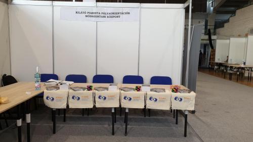 A képen, a Piarista Kilátó Központ standja látható. Az asztalokon kiadványok vannak elhelyezve.