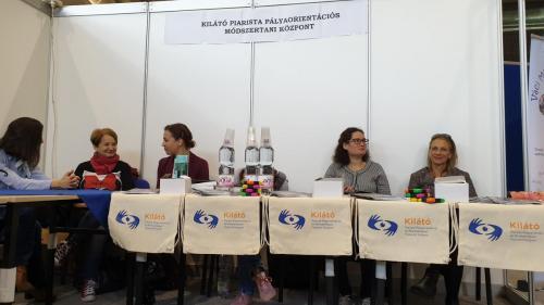 A képen a Piarista Kilátó Központ standja látható. Az asztalnál a tanácsadó munkatársak ülnek, akik a még kitöltetlen kérdőívekkel várják a fiatalokat.