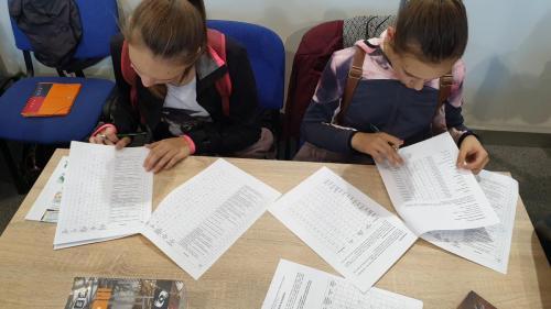 A képen két diáklány látható ahogy szorgosan tesztet töltenek az asztalnál ülve.